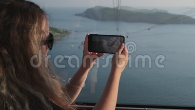 Woman capturing sea scenery from cable car in Phu Quoc, Vietnam. Woman tourist observing breathtaking seascape and taking mobile video of this scenery from cable stock footage
