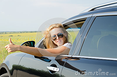 Woman in car giving a thumbs up