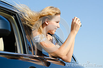 Woman in car taking photographs