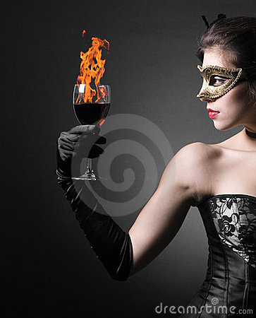 Woman in carnival mask and a  red wine.