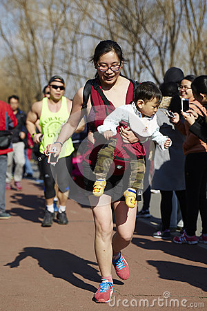 Free Woman Carrying Baby And Running In Beijing Color Run Event Royalty Free Stock Image - 73583416