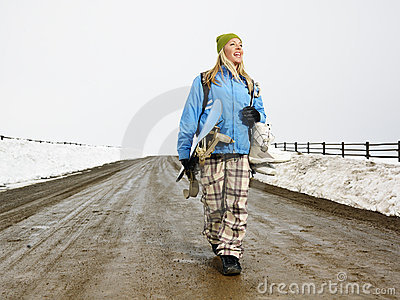 Woman carrying snowboard.