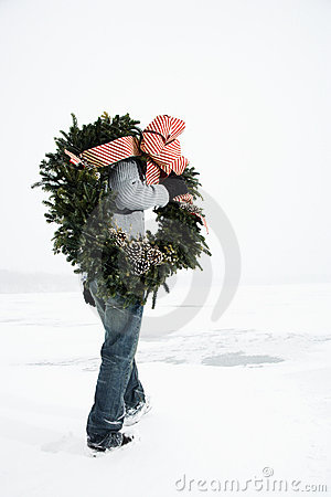 Woman Carrying Wreath Through Snow
