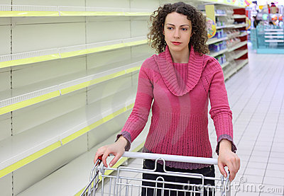 Woman with cart in shop with empty shelves