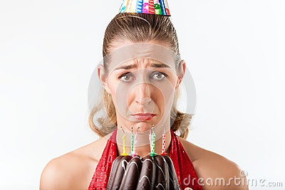 Woman celebrating birthday with cake candles wiped