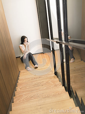 Woman On Cell Phone At Bottom Of Stairs