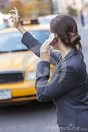 Woman on Cell Phone Hailing a Yellow Taxi Cab
