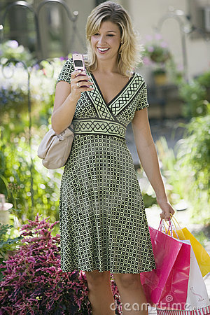 Woman with cell phone and shopping bags