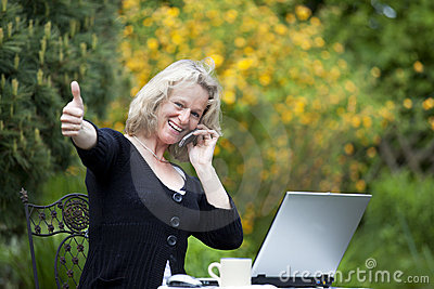 Woman with cellphone and laptop posing thumbs up