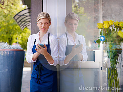 Woman with cellphone working as florist in shop