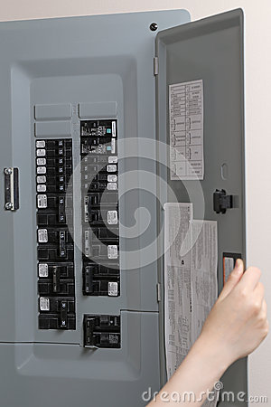 Woman Checking Automatic Fuses At Electrical Control Panel