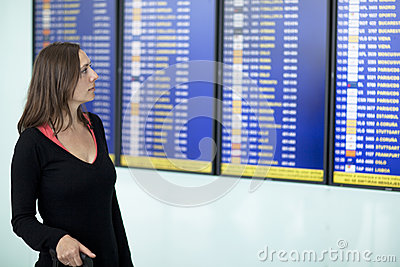 Woman checking destination board at the airport