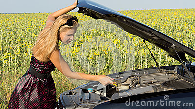 Woman checking her engine oil