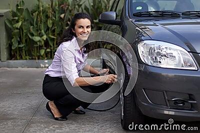 Woman checking tire pressure