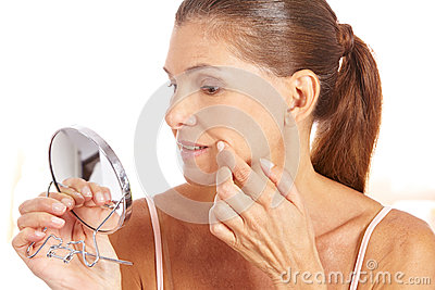 Woman checking wrinkles in mirror