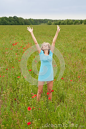 Woman cheering in  poppy field