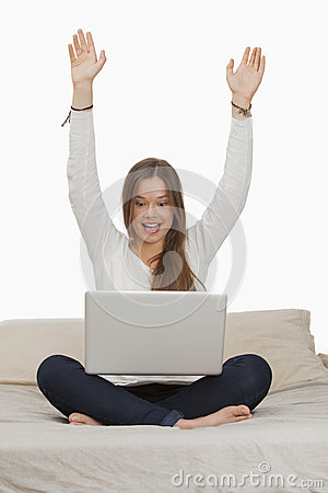 Woman cheering while working on a laptop