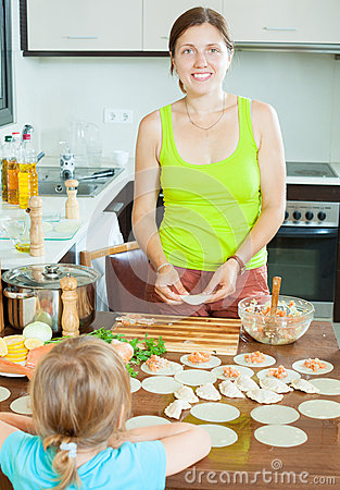 Woman with a child making fish dumplings freshest salmon stuffi