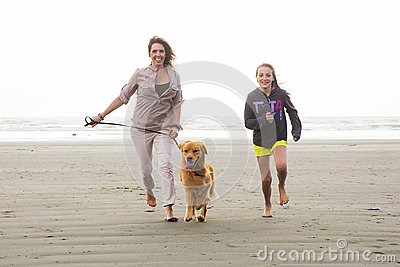 Woman and child running with a dog