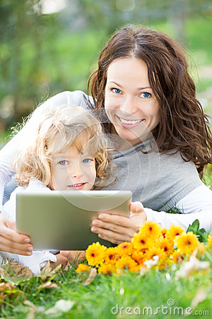 Woman and child using tablet PC outdoors