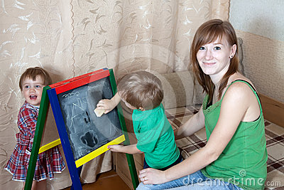 Woman and children draws on  blackboard