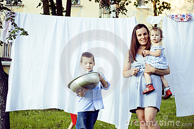 Woman with children in garden hanging laundry outside, lifestyle people concept Stock Photo