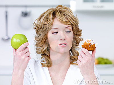 Woman choose between cake and apple
