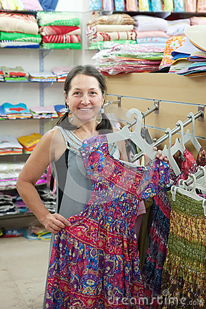 Woman  chooses dress at  shop