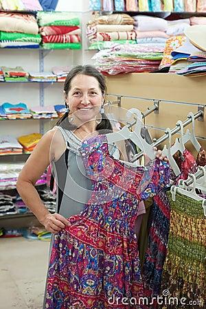 Woman  chooses dress at  shop
