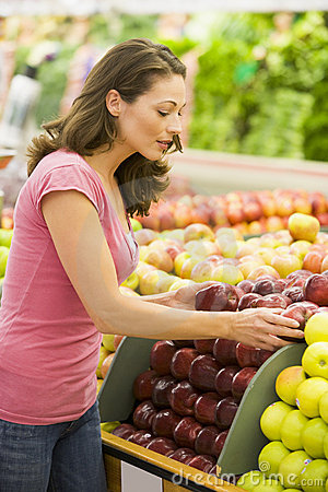 Woman choosing apples in produce department