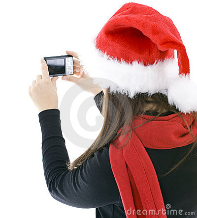 Woman in Christmas cap keeping digital camera