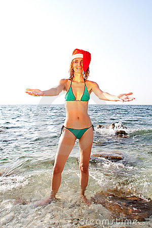 Woman in christmas hat inviting to sea