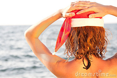 Woman in christmas hat looking at the sea
