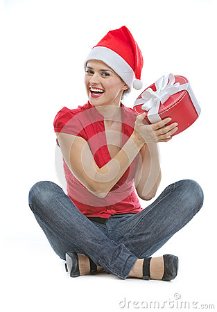 Woman in Christmas hat sitting on floor with gift