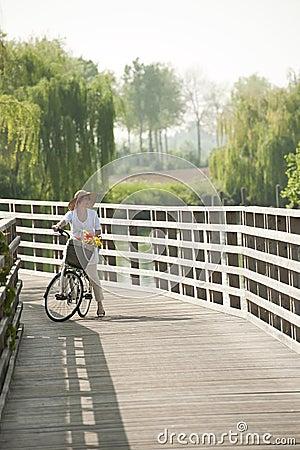 Woman ciclying on a bridge