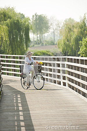 Woman ciclying on a bridge