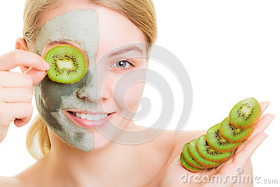 Woman in clay mask on face covering eye with kiwi Stock Photo