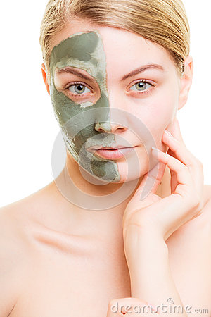 Woman in clay mud mask on face isolated on white. Stock Photo