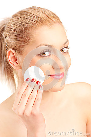 Woman cleaning her face with cotton pad