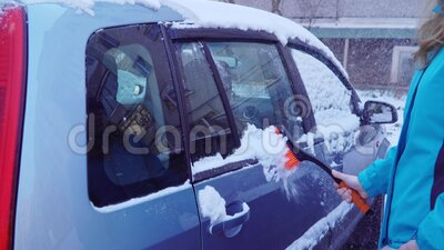 Woman cleans the car of snow with a brush.  stock video