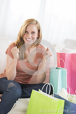 Woman Clenching Fists With Shopping Bags On Sofa