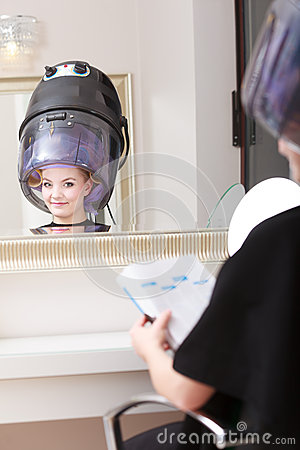 Woman client curlers in hair reads magazine hairdressing for Reading beauty salon