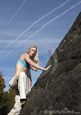 Woman climbing rock wall.