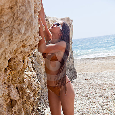 A woman is climbing up a rock