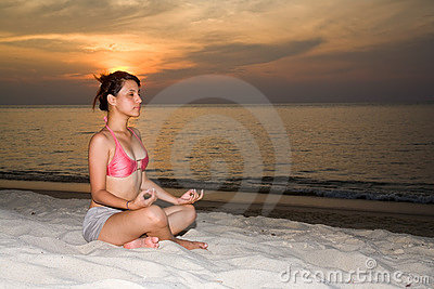 Woman closing eyes doing yoga on the beach