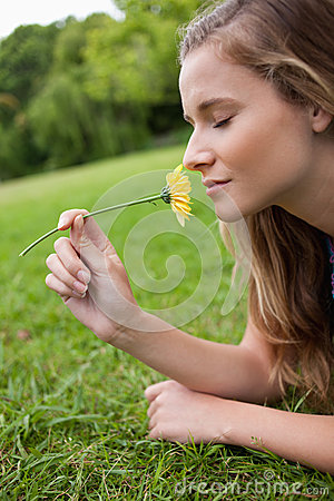 Woman closing her eyes while smelling a flower