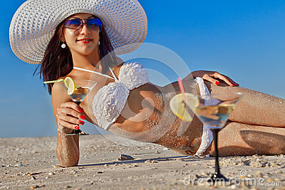 Woman with cocktail relaxing on beach