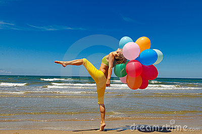Woman with colorful balloons on the beach