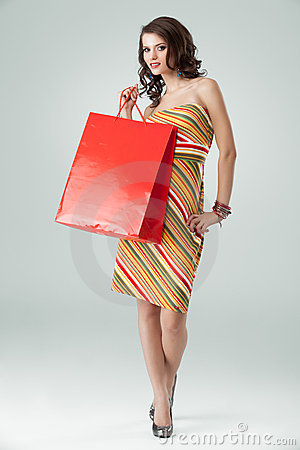 Woman colourful outfit holding red shopping bag