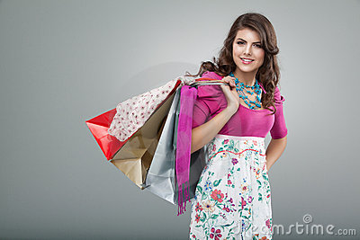 Woman in colourful outfit holding shopping bags